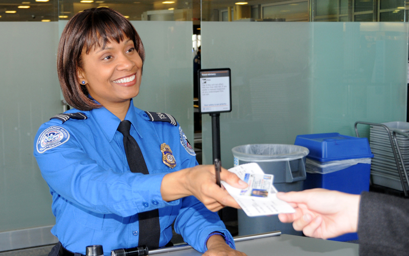 TSA officer checking passenger's ID.