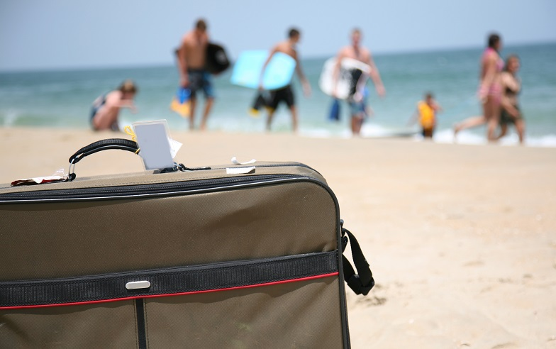 Luggage and people on a beach.