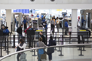 The new automated screening lanes at Newark Liberty International Airport allow several passengers to divest their belongings into bins simultaneously, speeding up the checkpoint process.