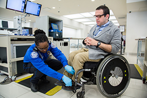 passenger in wheel chair being screened at the checkpoint