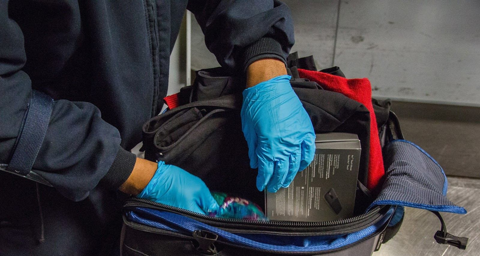 A photo of a TSA officer screening the checked baggage