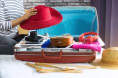 Summer travel items in open suitcase