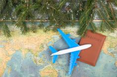 Plane and passport on a map next to evergreen tree branches