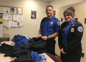 TSA officers Anthony Nicklo and Autumn Otis prepare the clothing to be donated (TSA photo).
