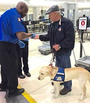 A TSA officer swabs the hands of one of the volunteers who went through the Greater Rochester International Airport checkpoint during an orientation session for a group of trainers and puppies from the Monroe Puppy Raising Region of Guiding Eyes for the Blind.