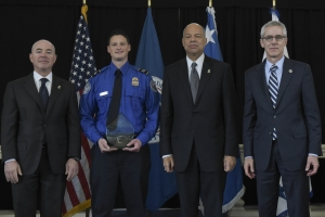 TSO Justin Sawhill, from Pittsburgh International Airport, holds his award and is joined by (from left) Deputy Secretary Alejandro Mayorkas, Secretary Jeh Johnson and Administrator Neffenger on Friday, May 13, 2016, in Washington, D.C.