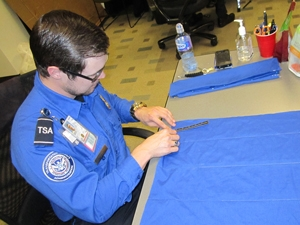 TSA officer working on sewing knapsack
