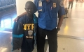 Lead TSA Officer Ravi Rampersad with young boy who came to LaGuardia Airport with his coat, but no shirt. Rampersad and a colleague purchased a T-shirt for the young boy. (TSA photo)